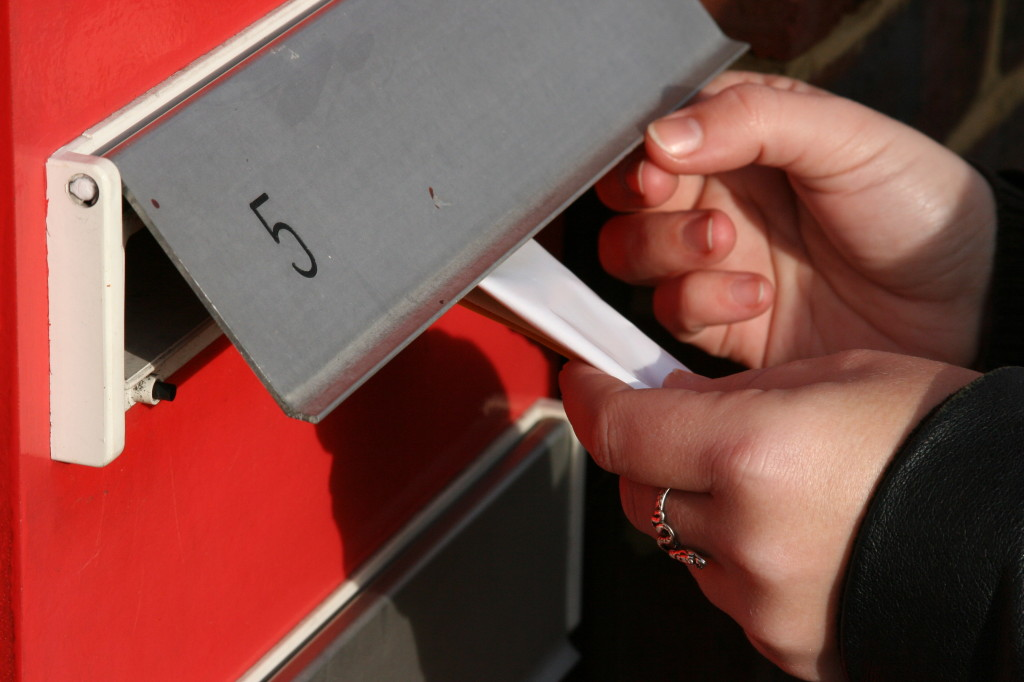 Woman Hand Pushing Leaflets In Mail Box